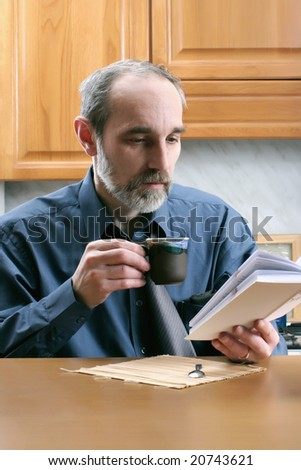 man reading book and drinking coffee on the kitchen at home