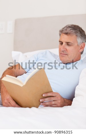 Man reading book in his bed