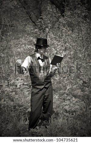 man reading book in old style dress. outdoor shot