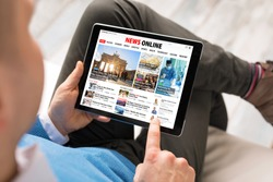 Man reading daily news online on tablet