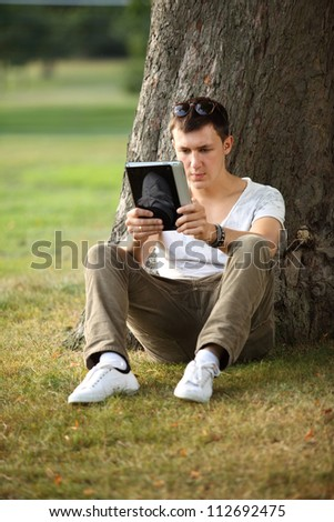man reading e-book in the park