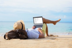 Man reading email on laptop while relaxing on beach