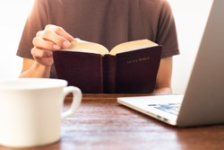 Man reading Holy Bible with laptop and a cup of coffee on the desk