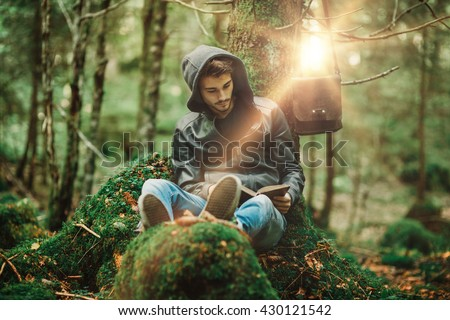 Man reading in nature and relaxing outdoors, freedom and individuality concept