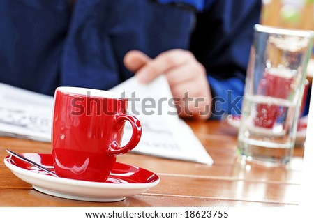 man reading newspaper drinking coffee and water