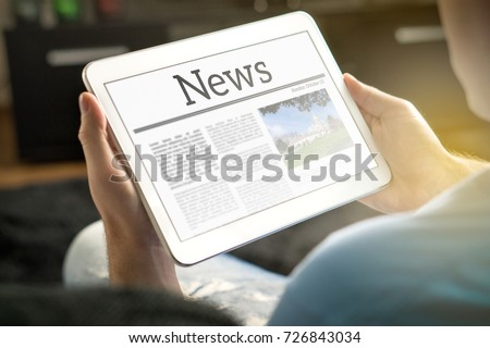 Man reading the news on tablet at home. Imaginary online and mobile news website, application or portal on modern touch screen display. Holding smart device in hand.