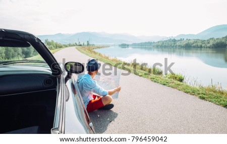Man reads roads map sitting near his cabriolet on picturesque mountain road