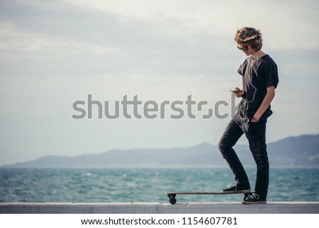 man ready to extreme ride wooden longboard skateboard. Good summer day for skateboarding