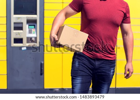 Man received a parcel using automated self-service post terminal machine or locker