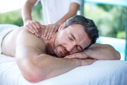Man receiving back massage from masseur in spa