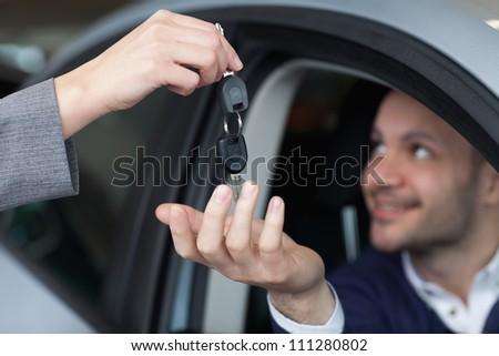 Man receiving car keys in his car