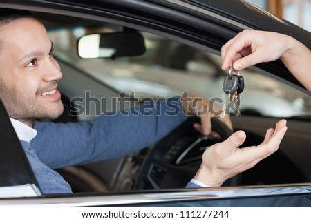 Man receiving keys while sitting in a car