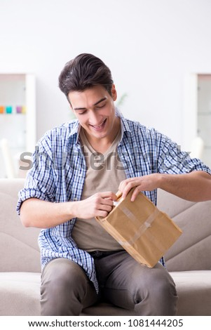 Man receiving parcel at home