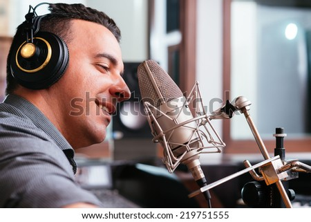 Man recording a song in the studio, side view