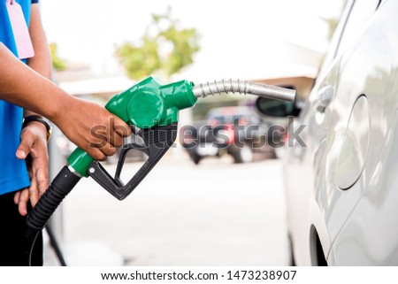 Man Refill and filling Oil Gas Fuel at station.Gas station - refueling.To fill the machine with fuel. Car fill with gasoline at a gas station. Gas station pump.  #1473238907