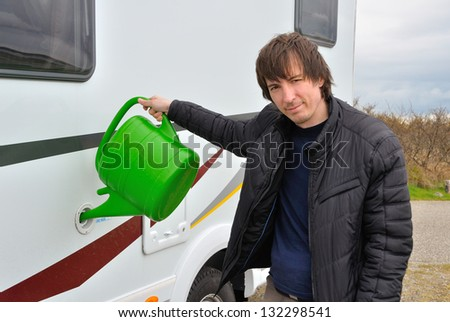 Man refilling camper (RV) water tank, traveling by motorhome