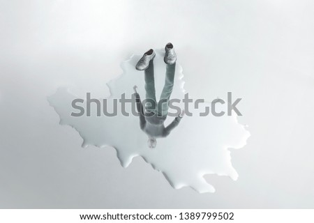 man reflection on a puddle; absence surreal concept