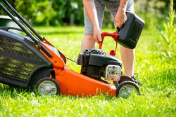 Man refueling the lawnmower on his huge garden, gardening concept