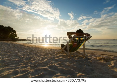 Man relax on chair beach in vacations with sunset and blue sky background. #330773795