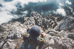 Man relaxing alone on rocky mountains cliff over clouds Travel Lifestyle emotions concept adventure active vacations outdoor top view