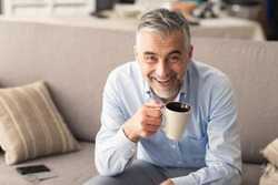 Man relaxing at home on the couch and having a coffee break, he is smiling at camera and holding a cup