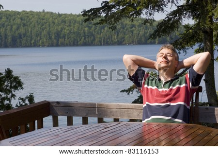 Man relaxing by a lake - stock photo