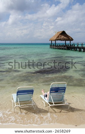 Man relaxing in a deck chair on the beach with a footbridge in the background