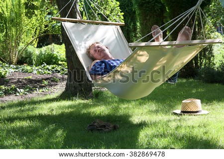 Man relaxing in a hammock in a summer garden