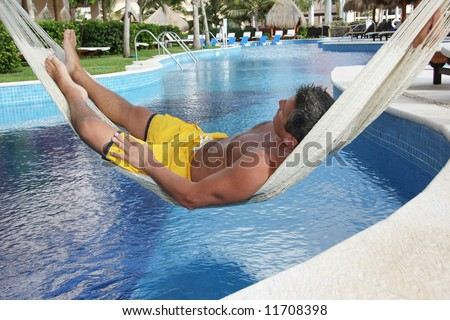 Man relaxing in a hammock over a resort pool.