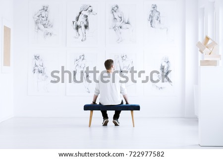 Man relaxing in art gallery while sitting on stool in front of white wall with drawings. Art gallery concept #722977582