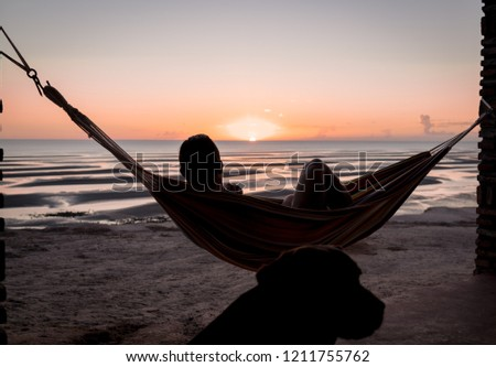 Man relaxing in his hammock watching the sunrise.  His dog and best friend by his side