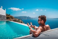 man relaxing in infinity swimming pool looking at the ocean,young man in the swimming pool relaxing looking out over the ocen caldera of Oia Santorini Greece
