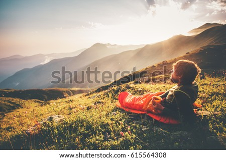 Man relaxing in sleeping bag enjoying sunset mountains landscape Travel Lifestyle camping concept adventure summer vacations outdoor hiking mountaineering harmony with nature