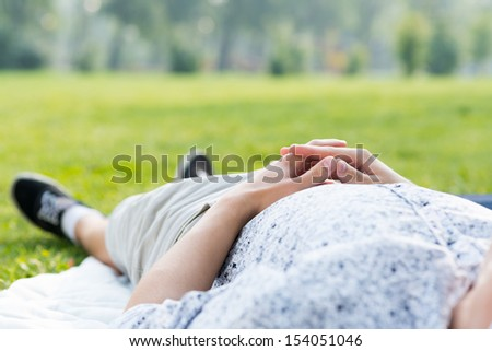 man relaxing in the park, close-up of linked hands on his stomach