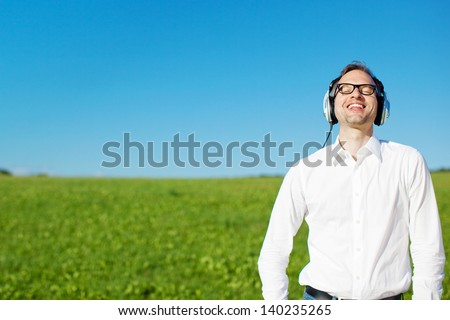 Man relaxing listening to music on headphones in a lush green field standing with his head tilted back to the sun