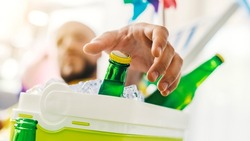 Man relaxing on a deckchair and taking a fresh beer from a cooler box, hand close up, selective focus