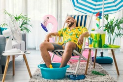 Man relaxing on a deckchair at home in the living room, he is having a staycation and pretending he is on a beach