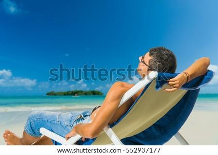 Man relaxing on beach, tropical ocean view #552937177