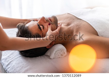 Man relaxing on massage table receiving massage. Young man is enjoying massage on spa treatment. Man relaxing in a wellness center. Male beauty - man receiving facial massage at luxury spa.