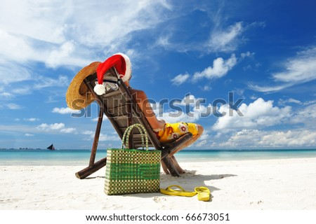 Man relaxing on the beach in santa's hat