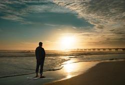 Man relaxing on the beautiful beach at sunrise. Sun  reflected on beach, Jacksonville, Florida, USA.