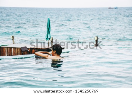 Man relaxing on the edge of an infinity swimming pool in luxury resort. Hotel travel vacation. Relaxation and summer holiday concept.