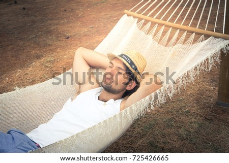 Man relaxing outside in a hammock #725426665