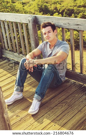Man Relaxing Outside. Wearing a gray T shirt, jeans, white sneakers, a young handsome guy is sitting on the wooden floor, back against fence in a remote location, relaxing.