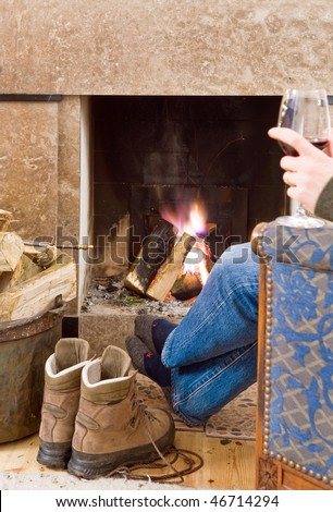 Man relaxing with a glass of red wine by the fireplace after a long hike; his boots off, next to him, warming up