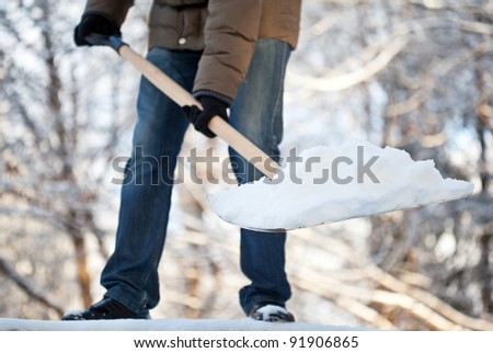 Man removing snow from a driveway with a shovel