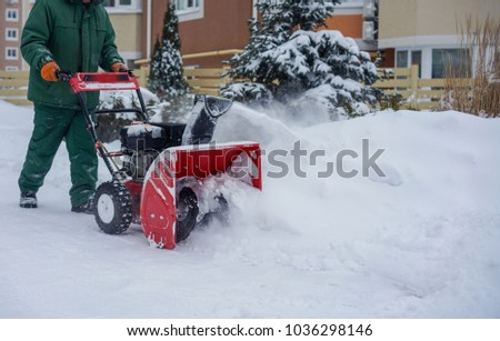 Man Removing Snow with a Snow Blower Winter #1036298146