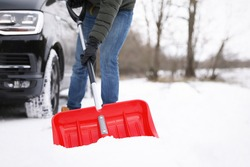 Man removing snow with shovel near car outdoors on winter day, closeup