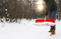 Man removing snow with shovel outdoors on winter day, closeup