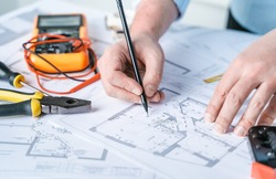 Man repairer making electricity project in house.Repairs planning.Drawing,diagrams,plan of electrification of apartment,building.Devices,accessories,voltmeter,wires,screwdriver,pliers and tape measure